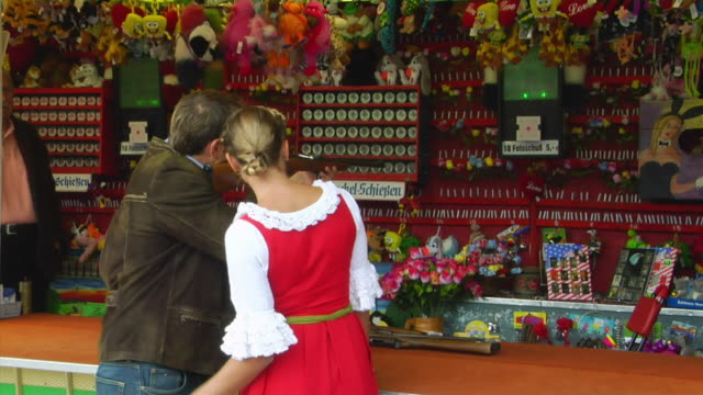 ms bavarian couple in traditional clothes at shooting gallery, oktoberfest, munich, germany - schießbude stock-videos und b-roll-filmmaterial