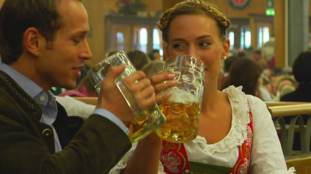 ms bavarian couple in traditional clothes drinking beer, oktoberfest, munich, germany - deutsche kultur stock-videos und b-roll-filmmaterial