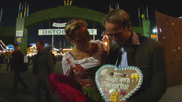 vídeos y material grabado en eventos de stock de ms bavarian couple in traditional clothes posing in front of oktoberfest fair entrance, munich, germany - escritura occidental