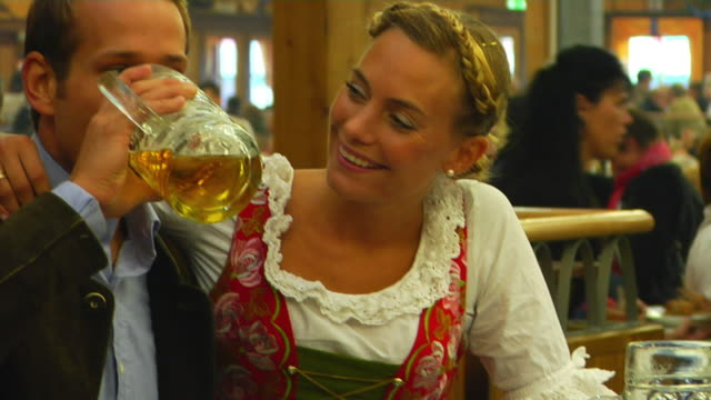 CU Bavarian couple in traditional clothes sitting side by side, Oktoberfest, Munich, Germany