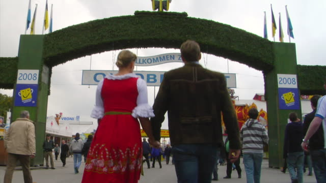 ws bavarian couple walking through oktoberfest entrance, munich, germany - baviera video stock e b–roll