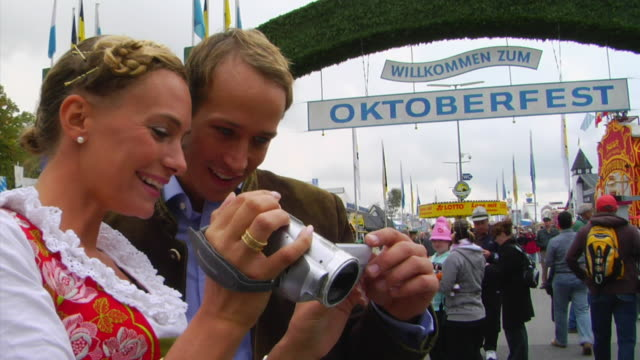 MS Bavarian couple watching video on camcorder in front of Oktoberfest entrance, Munich, Germany