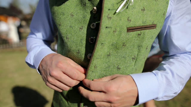bavarian men buttoning traditional clothes outdoor - traditional clothing stock videos & royalty-free footage