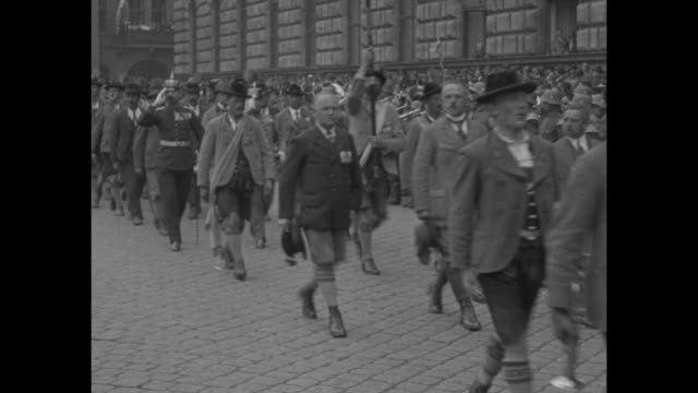 Bavarian soldiers on parade / musicians in ethnic dress in parade / men in lederhosen goose stepping / police using rope to hold back surging crowd /...