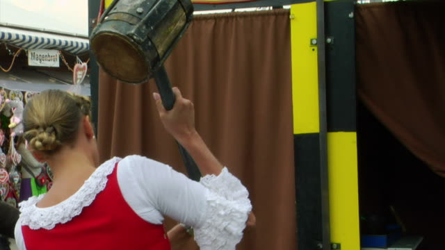 mu, bavarian woman in traditional clothes hitting button of high striker game, oktoberfest, munich, germany - fairground stall stock videos & royalty-free footage