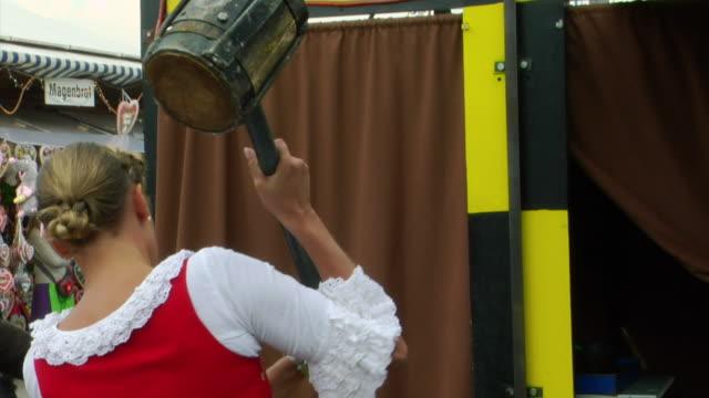 MU, Bavarian woman in traditional clothes hitting button of high striker game, Oktoberfest, Munich, Germany
