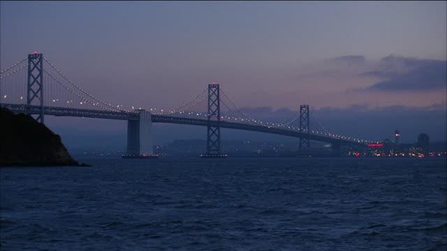 ws bay bridge at dusk / pan over san francisco bay to skyline / san francisco, california - 1995 stock videos & royalty-free footage