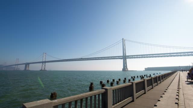 bay bridge over sea in blue sky. timelapse 4k hyperlapse - san francisco oakland bay bridge stock videos & royalty-free footage