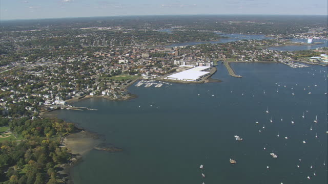 aerial bay shoreline, dozens of sailboats on open water, harbor facilities, and houses stretching to shore / salem, massachusetts, united states - salem stock videos & royalty-free footage