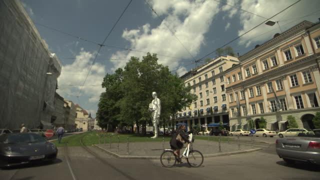 vídeos de stock e filmes b-roll de bayerischer hof, hotel, sculpture of graf von montgelas, trees, street, cars, people, - figura masculina