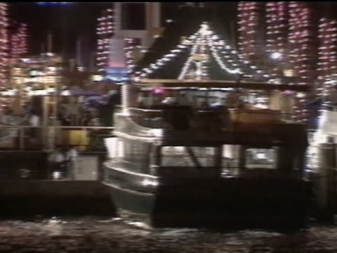 bayside marketplace w/ boats decorated w/ lights docked in marina. - biscayne bay stock-videos und b-roll-filmmaterial