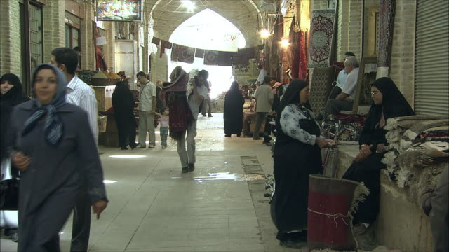 ws bazaar scene with man carrying bundle of carpets, shiraz, iran - iran stock videos and b-roll footage