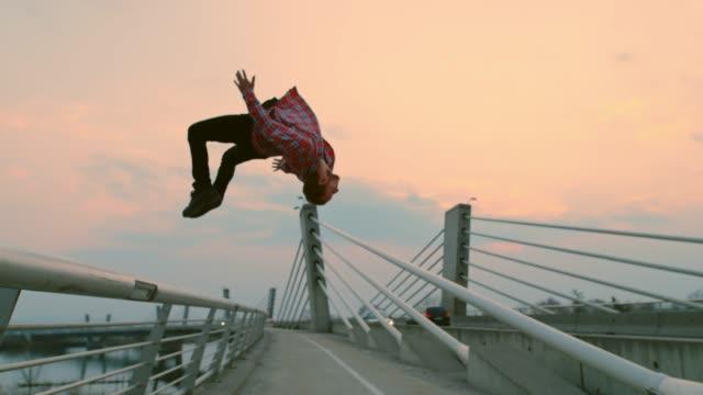 vídeos de stock e filmes b-roll de slo mo b-boy performing a backflip on the bridge - break dance