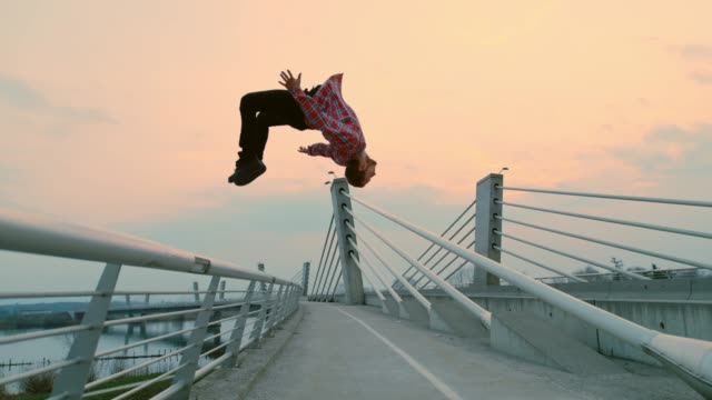 slo mo b-boy performing a somersault from a fence - vita cittadina video stock e b–roll