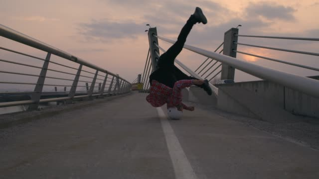 slo mo b-boy spinning on his head on the bridge - acrobatic activity stock videos & royalty-free footage