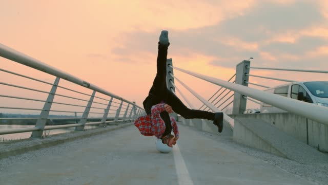 vídeos de stock e filmes b-roll de slo mo b-boy spinning on his head on the bridge - girar