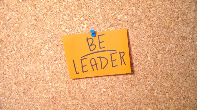 vídeos de stock e filmes b-roll de be leader word group on paper pinning up on corkboard by a man - papel adesivo