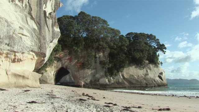 ws beach and cathedral cave, woman walking in distance / hahei, waikato, new zealand - new zealand点の映像素材/bロール