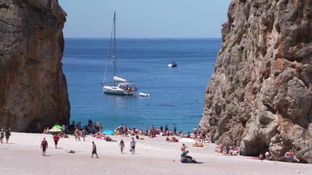 Beach and rocky coast with tourist at Cala Sa Calobra, Torrent de Pareis.