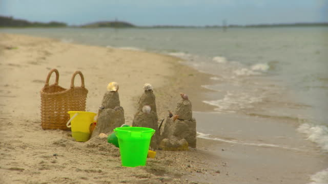 ms pan beach bag and pails next to sand castle on beach, eastville, virginia, usa - beach bag stock videos and b-roll footage