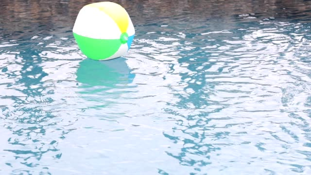 beach ball floating in refreshing swimming pool water. - floating on water stock videos & royalty-free footage