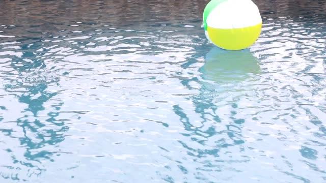 strandball schwimmt im erfrischenden schwimmbadwasser. - auf dem wasser treiben stock-videos und b-roll-filmmaterial