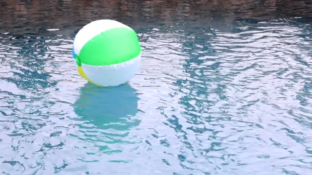 beach ball floating in refreshing swimming pool water. - sphere stock videos & royalty-free footage