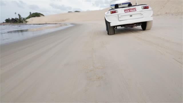 WS, PAN A beach buggy drives along the shore away from camera / Natal, Brazil