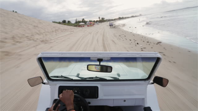 ws, pov a beach buggy drives along the shore / natal, brazil - dune buggy stock videos and b-roll footage