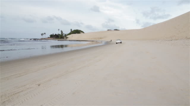 ws, pan a beach buggy drives along the shore towards camera / natal, brazil - dune buggy stock videos and b-roll footage