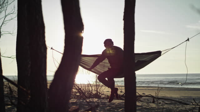 beach camping. hammock between two pines. lens flares - named wilderness area stock videos & royalty-free footage