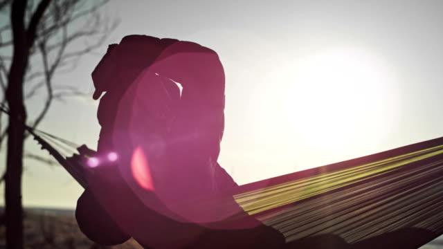 strandcamping. hängematten-entspannung. linsenfackel - langsam stock-videos und b-roll-filmmaterial