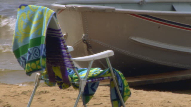 vídeos de stock, filmes e b-roll de beach chair and towel with boat in water in the background - toalha de praia