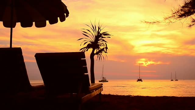 Beach chair and umbrella on tropical sunset beach