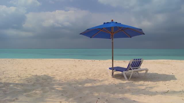 ws, beach chair under sun umbrella facing ocean, abaco islands, bahamas - beach umbrella stock videos and b-roll footage