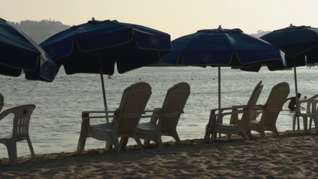 ms beach chairs and umbrellas at water's edge / acapulco, guerrero, mexico - アディロンダックチェア点の映像素材/bロール