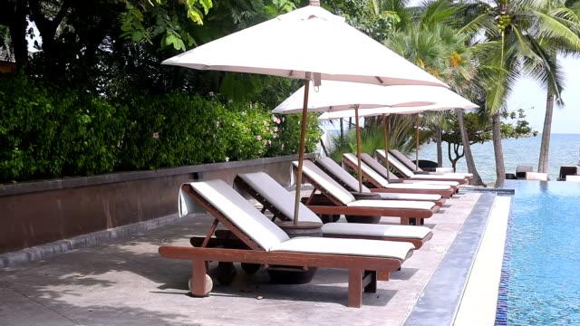 Beach chairs near swimming pool in tropical resort