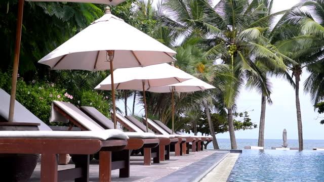 stockvideo's en b-roll-footage met strandstoelen in de buurt van zwembad in tropische resort - zonnescherm gefabriceerd object