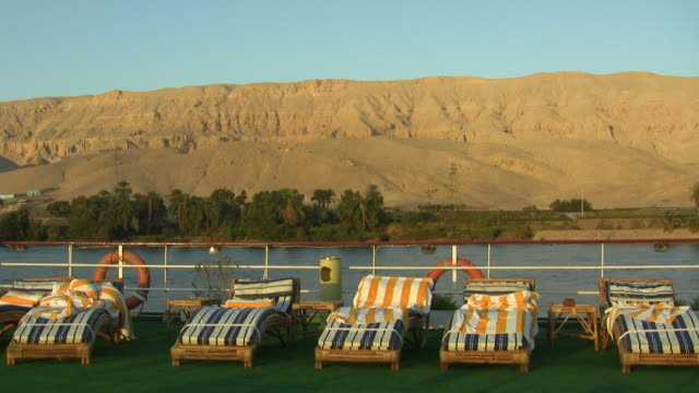 WS, Beach chairs on deck of cruise ship moving on Nile River, Egypt