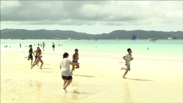 Beach Children running along the water's edge