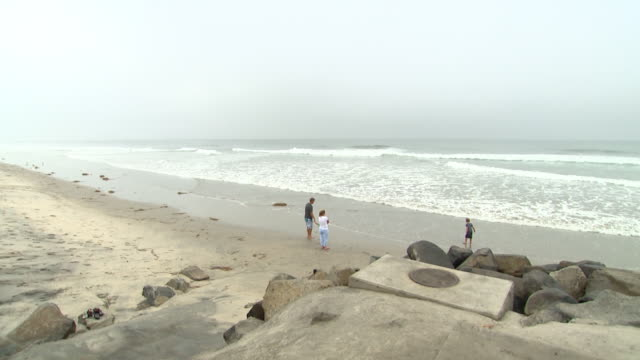 beach couple walking on beach waves cloudy beach lifeguard stand pan to beach man jogging on beach surfers going out into ocean pier surfer walking... - oceanside stock videos and b-roll footage