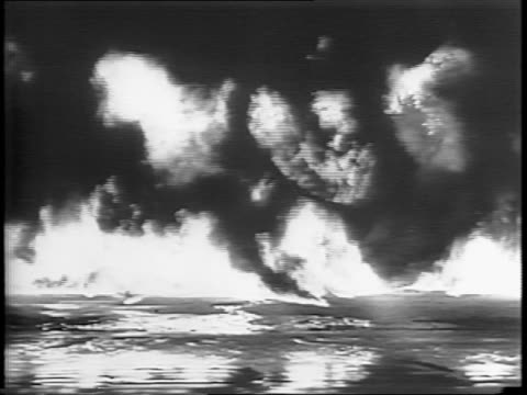 beach engulfed in flame and smoke / soldiers lift and position flammable oil drums / an explosion sets the area ablaze / wide shots of shoreline on... - flammable stock videos & royalty-free footage