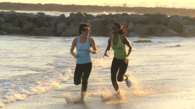 vidéos et rushes de beach fitness montage with two women - only women