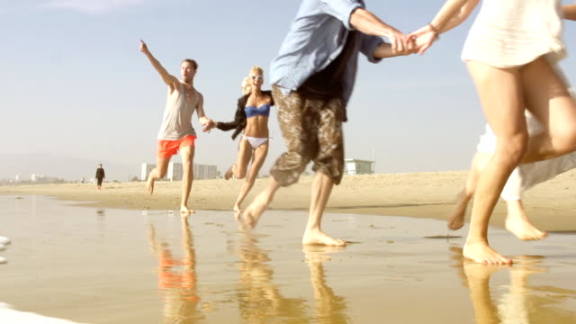 slow motion - beach friends group running - medium group of people stock videos & royalty-free footage