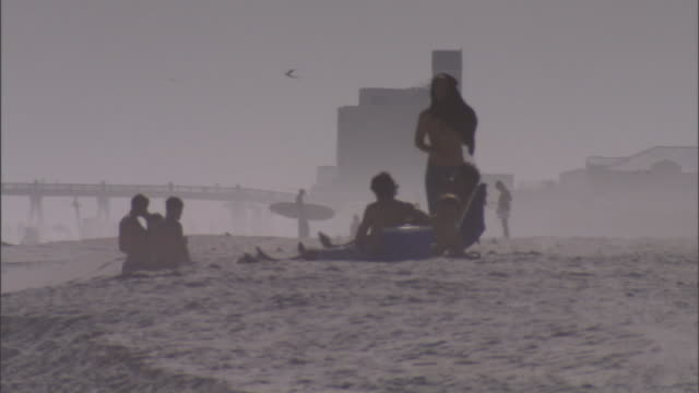 beach goers hang out on a dusty beach. - attending stock videos & royalty-free footage