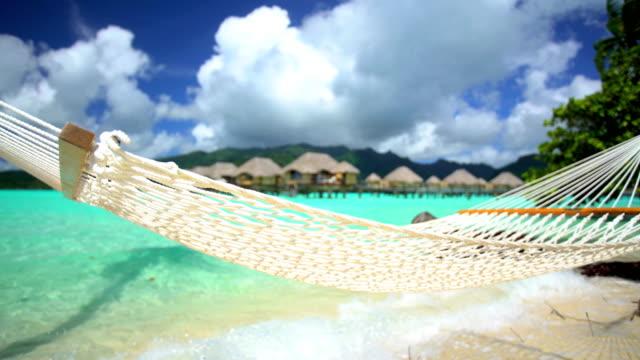 beach hammock overwater bungalows aquamarine lagoon bora bora - polynesian ethnicity stock videos & royalty-free footage