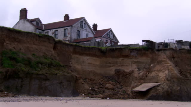 A beach house perches precariously along an eroded English coast. Available in HD.