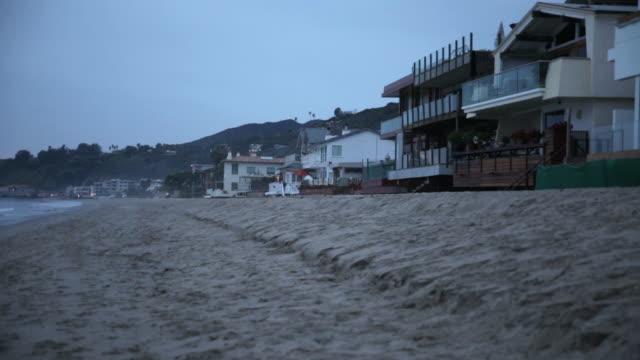 ws beach houses along beach at dusk - 見渡す点の映像素材/bロール