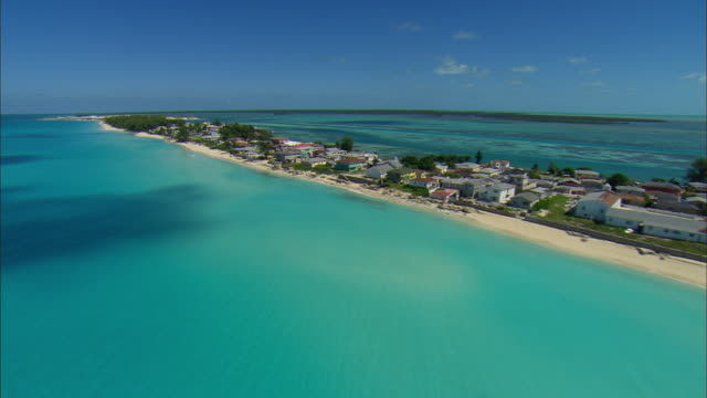 low aerial beach houses in alicetown, bimini island, bahamas - bimini stock videos & royalty-free footage