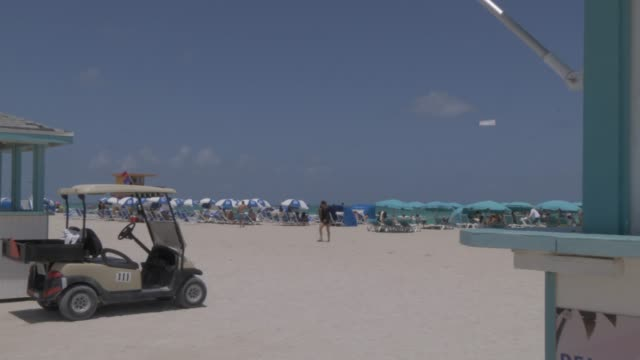 beach huts and american flag on miami beach, south beach, miami, florida, united states of america, north america - golf cart stock videos & royalty-free footage
